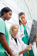 Female doctor and nurses look at CT scan