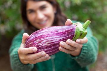 caucasian woman holding eggplant.