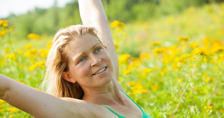 woman arms stretched high in meadow of yellow flowers