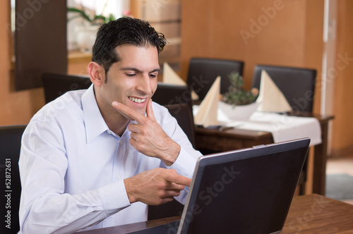 Mann deutet lachend auf Notebook