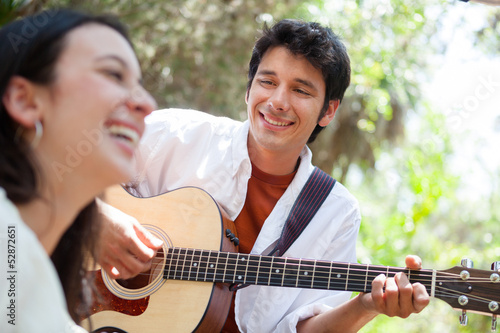 Young man playing guitar for woman