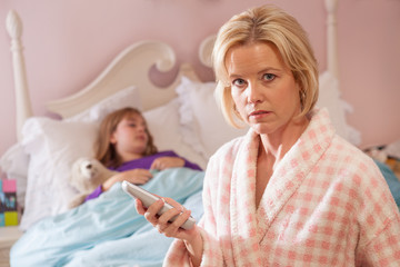Mother holds telephone while daughter sick in bed.