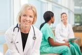 smiling female doctor sitting with female nurses