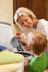 Mother and son putting clothes in washing machine.