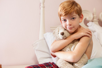 Young boy sitting on bed smiling at camera.