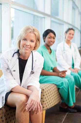 smiling female doctor sitting with smiling female nurses