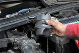 Mechanic replacing fuel filter at car diesel engine