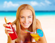 Woman with cocktail and sunblock on the beach
