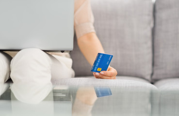 Closeup on credit card in hand of woman with laptop