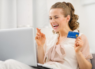 Happy housewife with laptop and credit card crossed fingers