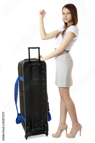 Slim girl teen stands next to huge, black suitcase on wheels.