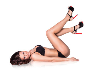 Woman in sexy lingerie and high-heeled shoes lying on her back.