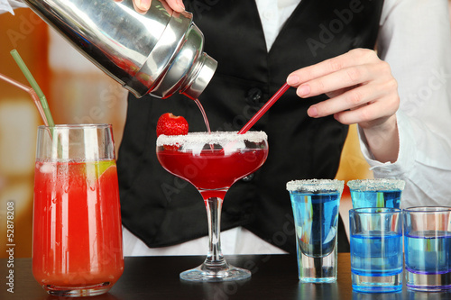 Barmen hand with shaker  pouring cocktail into glass,