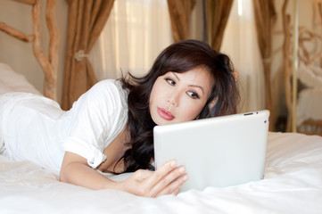 Asian woman holding a tablet lying on her bed