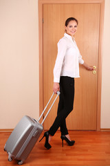 Young businesswoman with suitcase leaving room