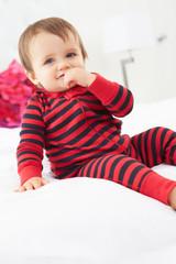 Toddler Sitting On Bed Wearing Pajamas