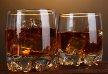 Brandy glasses with ice on wooden table on brown background