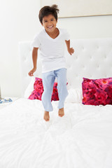 Boy Jumping On Bed Wearing Pajamas