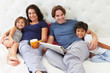Family Relaxing In Bed With Coffee And Newspaper