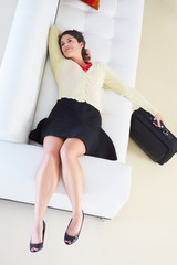 Tired Woman Lying On Sofa After Returning From Work