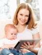 mother and baby with tablet computer on the couch at home