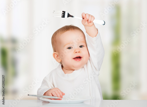 Funny baby with a knife and fork eating food - 52882287