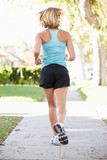 Rear View Of Female Runner Exercising On Suburban Street