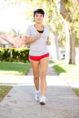Female Runner Exercising On Suburban Street