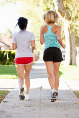 Rear View Of Two Female Runners On Suburban Street