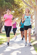 Group Of Female Runners Exercising On Suburban Street