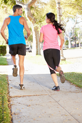 Rear View Of Couple Running On Suburban Street