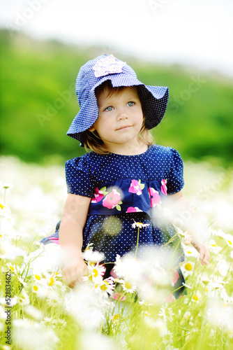 sweet toddler in daisy field