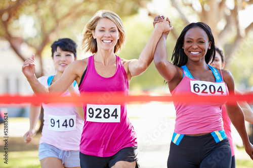 Two Female Runners Finishing Race Together - 52883624