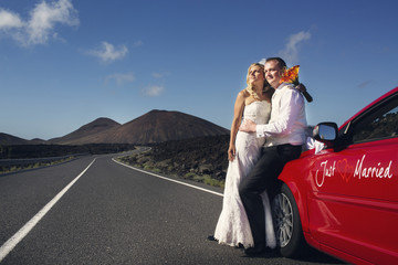 "Newlyweds on the road next to the car ""Just Married""."
