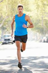 Male Runner Exercising On Suburban Street