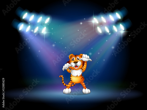 A tiger raising her hands at the stage under the spotlights