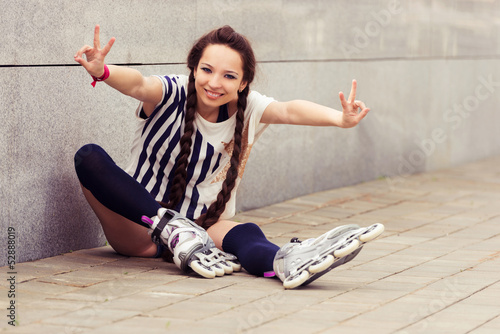 girl going rollerblading sitting putting on inline skates
