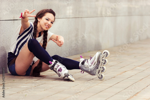 happy teenager on rollerblading sitting on street