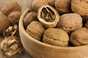 Walnuts in wooden bowl on burlap