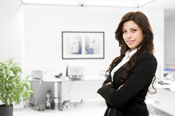 Young smiling business woman posing on office background