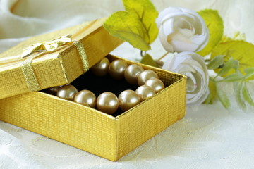 pearl necklace in a gold gift box