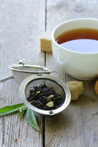 black tea leaves in a metal strainer on a wooden table