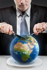 Greedy businessman cutting planet Earth