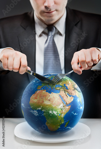Greedy businessman cutting planet Earth