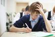 school boy struggling to finish test in class.