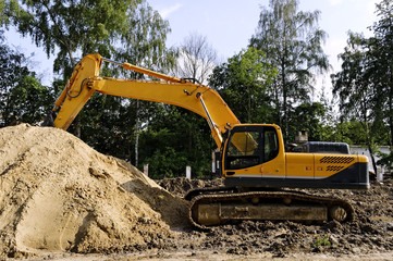 Excavator near the heap of sand