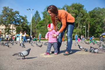 Child girl and mum playing with doves in the city street