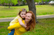 Daughter and mother piggyback smiling in park outdoor