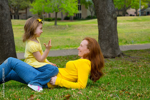 Daughter and mother playing counting lying on lawn