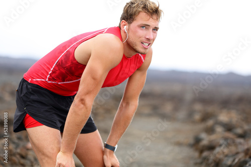 Runner man resting with music after running